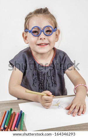 Blond cute little girl with blue glasses painting on a school desk in front of white background