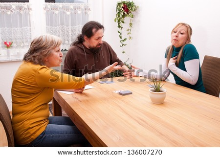 blond daughter cheating in card games with family - stock photo