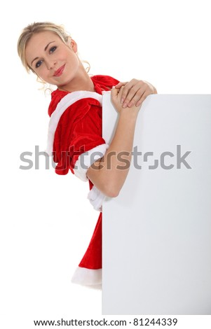 Blond dressed in Santa outfit stood with message board
