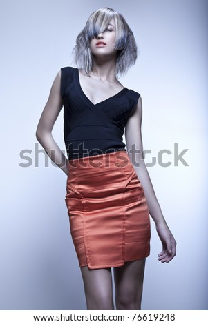 Blond fashion model with modern haircut and red skirt in studio with blue background - stock photo