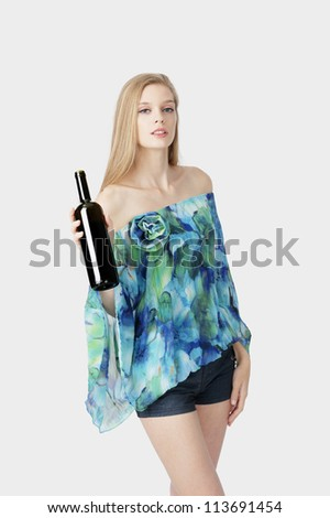 blond fashion model with short pants holding wine bottle posing at light background - stock photo