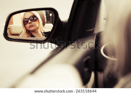 Blond fashion woman in sunglasses looking in the car mirror  - stock photo