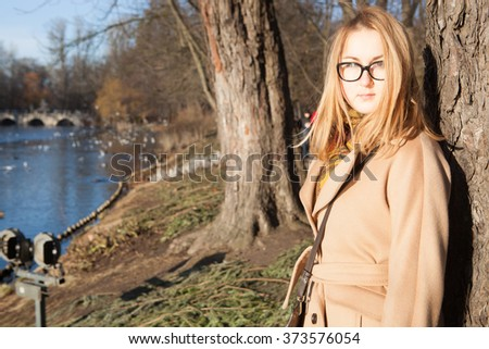 Blond fashion woman walking outdoor against an autumn nature landscape - stock photo