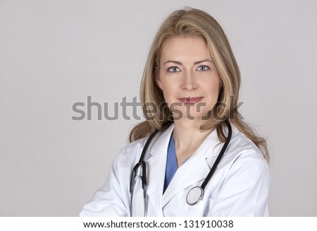 blond female doctor posing on light grey background - stock photo