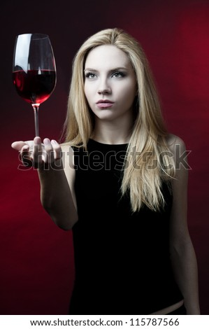 blond female fashion model holding wine glass posing at red background