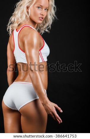 Blond female in a white sexy sportswear isolated on a black background.