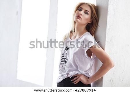 Blond female in a white t shirt posing in a light. - stock photo