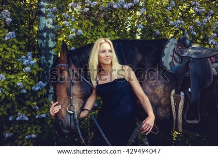 Blond female in black evening dress posing with brown horse.