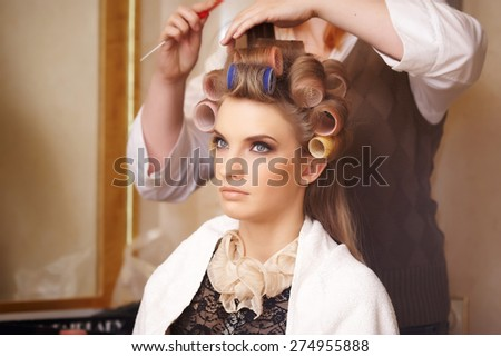 Blond female in hair salon. Hairdresser on background - stock photo
