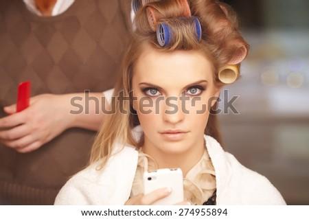 Blond female in hair salon. Hairdresser on background - stock photo