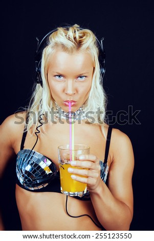 Blond female in mirror bra in headphones and with glass of orange juice. Isolated on black.