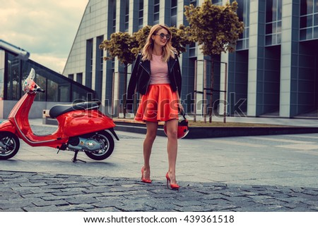 Blond female in red skirt going away from red moto scooter. - stock photo
