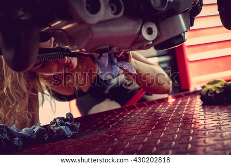 Blond female in sexy black clothes cleaning a motorcycle - stock photo