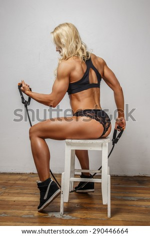 Blond female in sexy sportswear doing exercises with expander. - stock photo