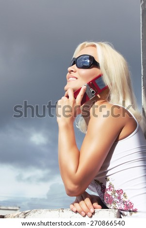 Blond female in sunglasses listening music.