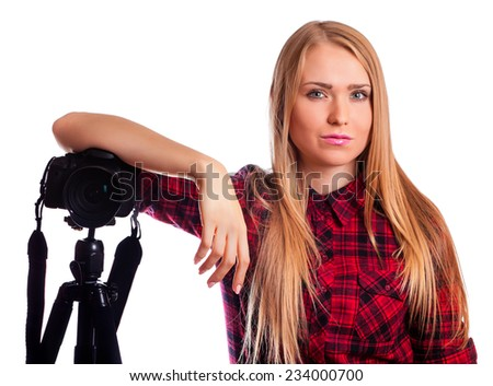 Blond female photographer stand near a professional camera - isolated over white - stock photo