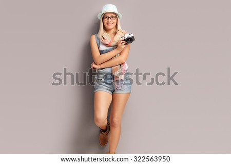 Blond female photographer with a blue hat holding a camera and leaning against a gray wall - stock photo