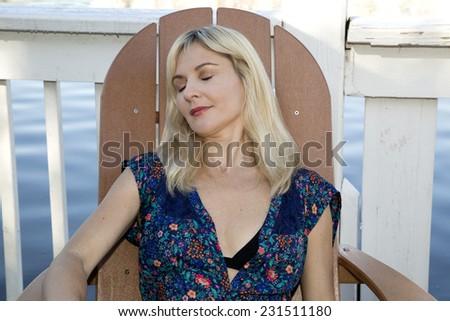 blond female relaxing wearing swimwear at lake - stock photo