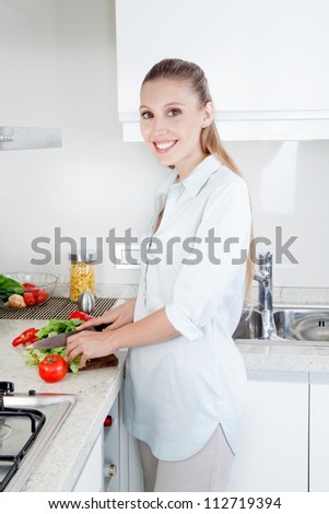 Blond female woman cutting vegetables in kitchen