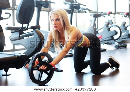 Blond fitness female doing exercises with fitness roller in a gym club.