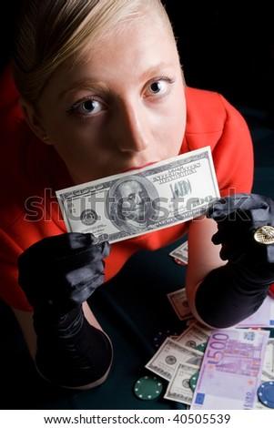 Blond gambler kissing a dollar note - stock photo
