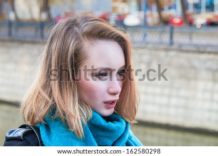 Blond Girl at embankment in Moscow with bridge in background