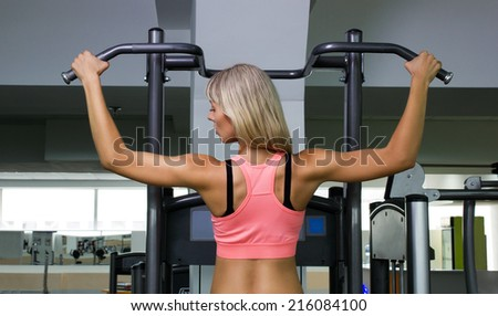 blond girl doing athletic  exercise  in gymnasium - stock photo