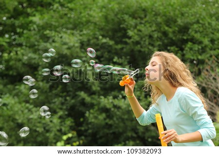Blond girl doing huge bubble soap outside in a park