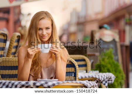 Blond girl drinking coffee and smiling. - stock photo