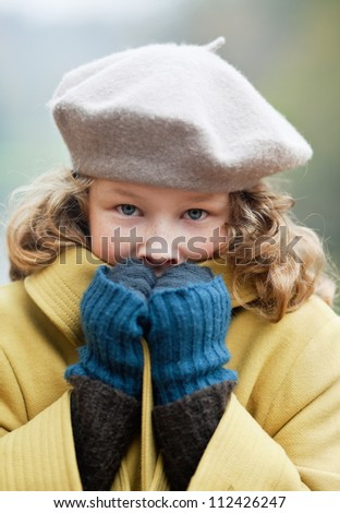 Blond girl freezing up in a cold autumn day