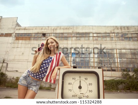 Blond girl holds hand on her glasses standing on damaged gas station - stock photo