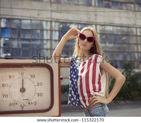 Blond girl holds hands on her glasses standing on damaged gas station - stock photo