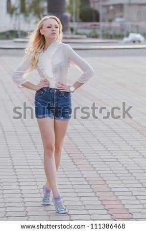 Blond girl in a blue jeans shorts walking down the street - stock photo
