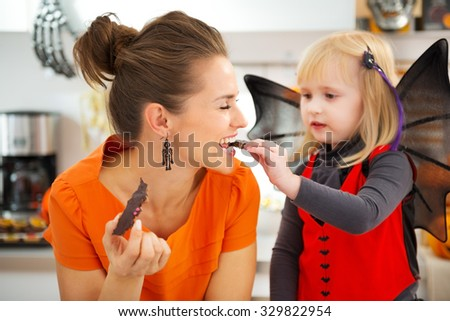 Blond girl in bat costume with happy mother in decorated kitchen eating freshly homemade Halloween biscuits for Trick or Treat. Traditional autumn holiday - stock photo