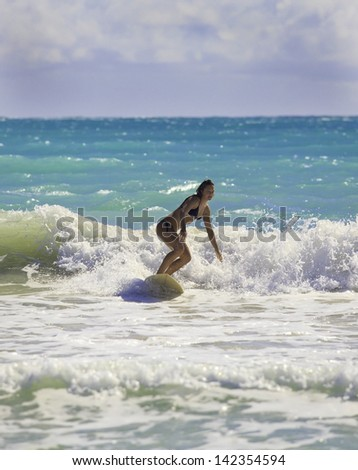 blond girl in bikini surfing the waves in hawaii