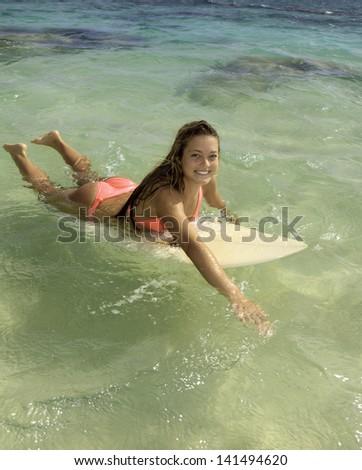 blond girl in bikini with her surfboard - stock photo