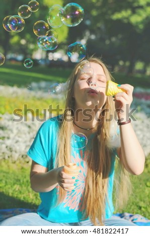 Blond girl in casual clothes blowing soap bubbles in a sunlit summer park sitting on grass