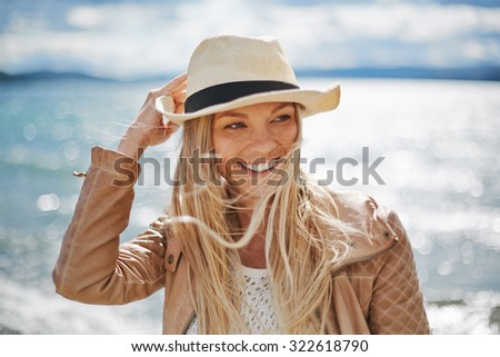 Blond girl in hat spending leisure by the seaside - stock photo