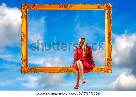 blond girl in red coat sitting on a picture frame - stock photo