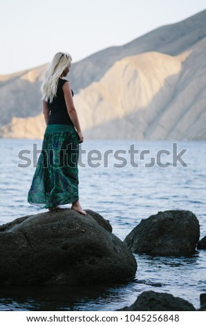 Blond girl is standing on the beach and looking at the mountains. Summer vacation by the sea.