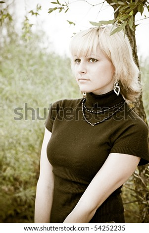 blond girl looks in distance, nature - stock photo