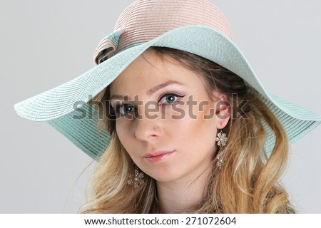 Blond girl, portrait in turquoise hat, close up view