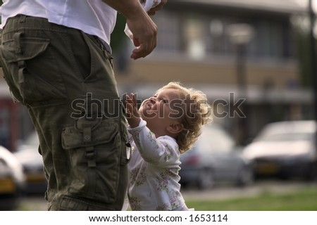Blond girl reaching up to daddy to pick her up