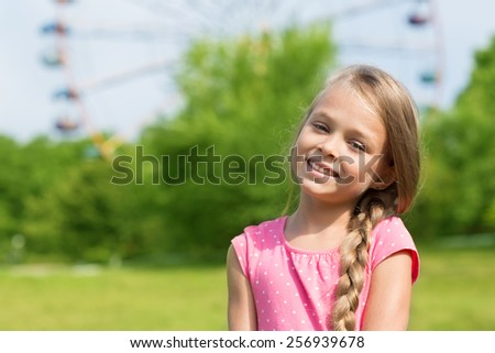 Blond girl seven years at an amusement park. Girl seven years. - stock photo