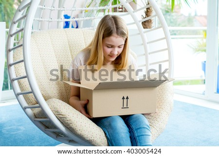 blond girl sitting in chair and opening a package - stock photo