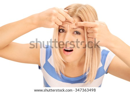 Blond girl squeezing a pimple on her forehead and looking at the camera isolated on white background - stock photo