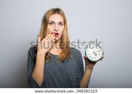 blond girl startled looks at the alarm clock, with clean skin, lifestyle concept studio photo isolated on a gray background