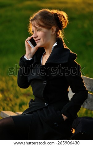 Blond girl talking on cell phone sitting on a bench at sunset - stock photo