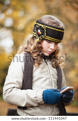 Blond girl texting with her cellphone while walking in an autumn park