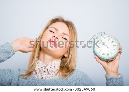blond girl wants to sleep with an alarm clock, wearing glasses isolated on a gray background